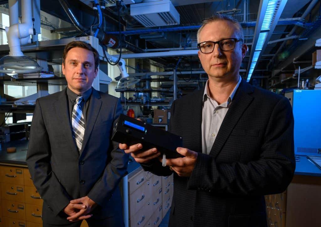Ervin Sejdic, PhD (links) en Alexander Star, PhD, houden het prototype van hun THC-detecterende apparaat omhoog.